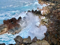 Blue waters of Hawaii crashing over the rocks at the Mackenzie State Recreation Area on the Big Island