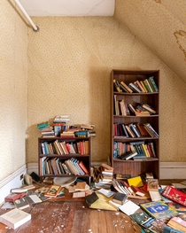 Books forgotten on their shelves in this abandoned nursing home
