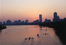 Boston rowing down the Charles River at dusk