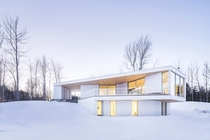 Bright white home blends with snowy landscape in Quebec Canada by MU Architecture Photo Ulysse Lemerise Bouchard