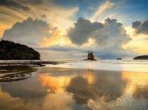 Building clouds and a setting sun reflect on a sandy beach on Costa Ricas Nicoya Peninsula Patrick di Fruscia