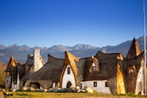 Built by hand and made entirely of clay towers of stone the walls built of a mixture of clay straw water and sand interior finishes with each bed table chair plate amp decorative object are handmade Castelul de Lut Valea Znelo in Transylvania Romania is a
