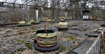 Bumper cars riddled with rust sit in a fairground in Pripyat