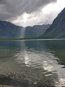 Burst of sunshine through the clouds on a rainy day at Lake Bohinj Slovenia