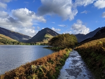 Buttermere lake in Lake District UK with grass and paths washed by the mountain springs all around
