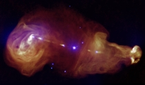 C showing jets generated by a supermassive black hole at the center of the galaxy where the galaxy is seen as a tiny point at the center of the giant plumes Composite image from observations by Chandra and the VLA