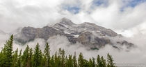 Canadian Rockies Rise Through the Clouds Above Banff