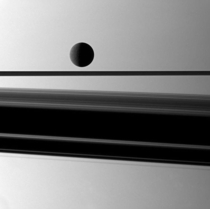 Cassini catching a glimpse of the ice moon Rhea through Saturns rings