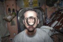 Chris Hadfield watches a water bubble float freely between him and the camera