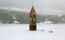 Church steeple peeking out of a frozen lake in the village of Graun