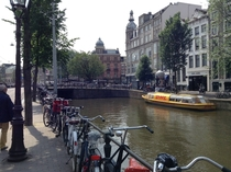 Classic Amsterdam sea of bikes canal DHL delivery boat