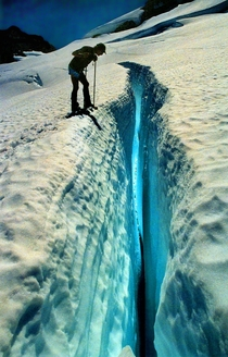 Climber peering down a blue crevasse on Mt Olympus WA