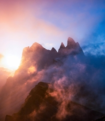 Clouds breaking at sunrise over the peaks of Sass Rigais Italy