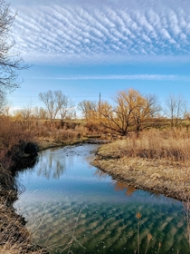 Clouds reflecting off a stream in Loveland Colorado