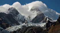 clouds taking over the mountains towering over the glacier in Cordillera Huayhuash Peru