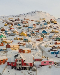 Colorful houses dotted across the snowy landsacpe in the town of Qaqortoq Kujalleq southern Greenland