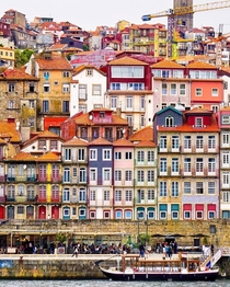Colorful houses in the historic Ribeira neighborhood facing the Douro River flowing through Porto Portugal