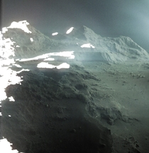 Colorized and slightly processed image of Comet Ps surface taken by Rosetta on September   Within a year part of the cliff on the lower left had collapsed due to the comets activity