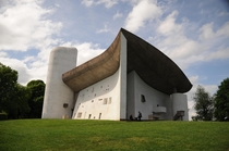 Completed in  Le Corbusiers Ronchamp chapel was built for a Catholic church on a pre-existing pilgrimage site The monumental curved concrete roof is a shell structure supported by columns hidden in the walls A gap underneath allows a sliver of light to fi