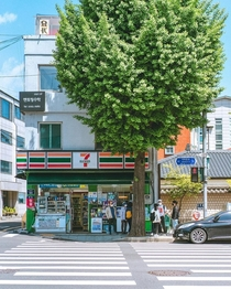 Convenience store next to a lush street tree near downtown Seoul South Korea