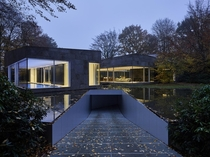 Cool house by DDM Architectuur with a driveway that goes under the pond in Antwerp Belgium