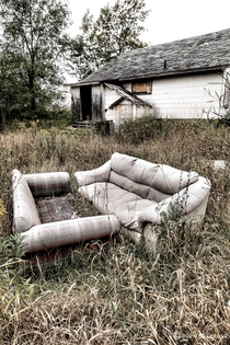 Couches left out to rot behind an abandoned home in Belleville Ontario