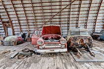 Couple of old trucks in various stages of restoration inside an abandoned barn in Southern Ontario
