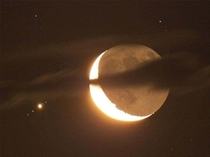 Crescent moon and Jupiter with four of its moons