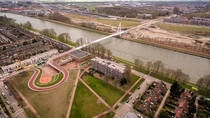 Cycling and walking bridge in Utrecht that uses a school roof as an approach ramp