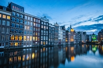 Damrak Amsterdam reflected in the water  Photographed by Simon van Ooijen