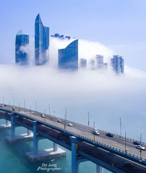 Double-decked Gwangan Bridge passing by a cluster of residential skyscrapers engulfed in sea fog Busan South Korea