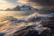 Dramatic morning light on crashing waves Lofoten Norway