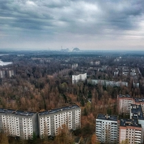 Drone shot over Pripyat and reactor  in the distance -