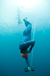 Dropping weighted and blindfolded  feet underwater on a single breath-hold during Waterman survival course For surfers and freedivers