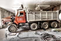 Dump truck left to rust in a heavy machinery garage after a fire decimated the upper floors