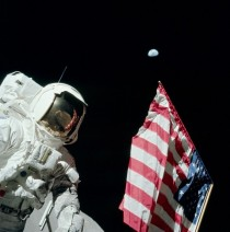 During the first EVA of Apollo  Eugene Cernan photographed Harrison Schmitt with the American flag and the Earth km away in the background Cernan is visible in the reflection in Schmitts helmet visor