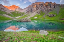 Early morning light over a field of wildflowers and crystal blue lake in the San Juan Mountains Colorado  by Jason Hatfield