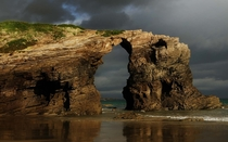 Early morning rain clouds over Las Catedrales beach in Ribadeo Spain