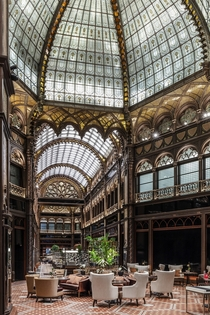 Eclectic reception area under a glass dome in Prisi UdvarParis Court a former bank building built in the s which was recently restored and renovated into a luxury hotel in downtown Budapest Hungary
