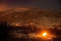 Embers from a wildfire smolder along Lytle Creek Road near Keenbrook California  by Noah Berger