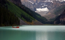 empty canoes resting on the calm water of Lake Louise in Alberta Canada  OP