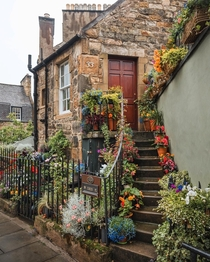 Entrance to a stone cottage adorned with flowers in Stockbridge Edinburgh Scotland
