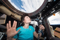 ESA Astronaut Samantha Cristoforetti in space wearing a Star Trek shirt doing a Vulcan salute