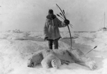 Eskimo polar bear hunter stands over his kill -