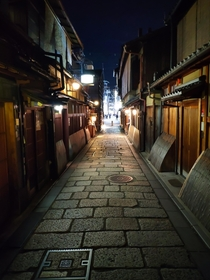Evening in quiet side street of Kyoto giving way to a busy main street