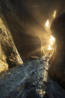Every winter there is a period where the setting sun lines up with this little slot canyon creating beautiful rays from the waterfall within Gotta love the southwest coast of Vancouver Island  tristantodd