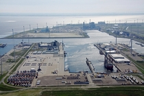 Factory that makes wind turbines surrounded by wind turbines about to ship some offshore wind turbines Eemshaven Netherlands