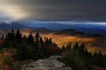 Fall foliage colors a line of mountains in Chatham New Hampshire as unsettled weather begins to clear on October