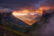 Fiery sunrise light erupts through a break in the clouds over the peaks of Glacier Montana  photo by Nagesh Mahadev