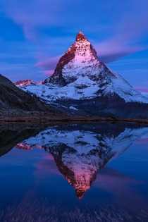 Firat Glow - First glow on an october morning at Riffelsee The Matterhorn in Switzerland by Roland Moser
